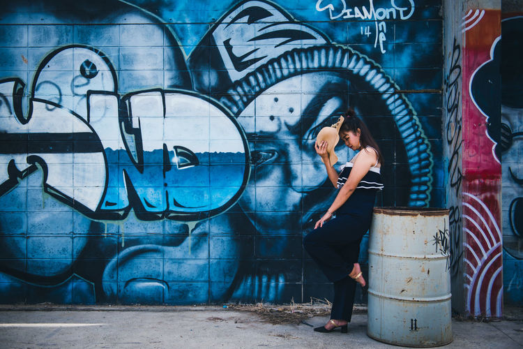 Side view of woman standing against graffiti wall