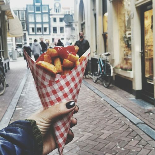 Cropped Image Of Woman Holding Snacks In Paper Cone At Street