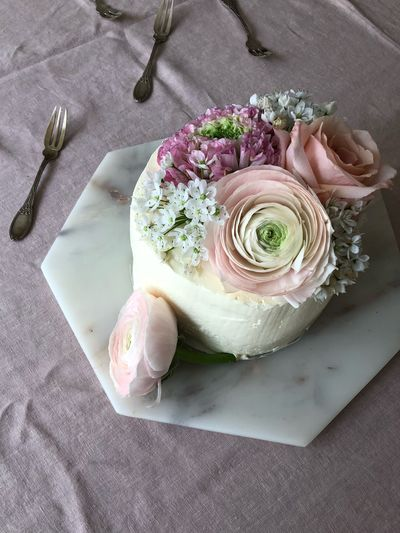 High angle view of cake with rose bouquet on table