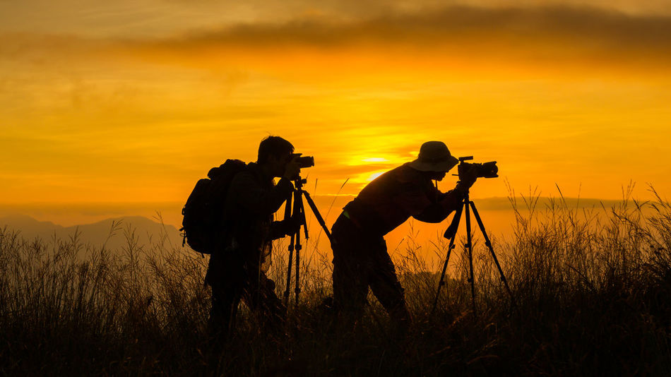 Adult Beauty In Nature Camera - Photographic Equipment Field Full Length Grass Holding Lifestyles Men Nature Occupation Orange Color Outdoors People Photographer Photographing Photography Themes Real People Silhouette Sky Sunset Technology Tripod Two People Water