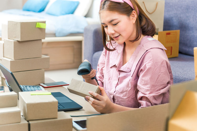 Woman scanning cardboard box with bar code reader at home