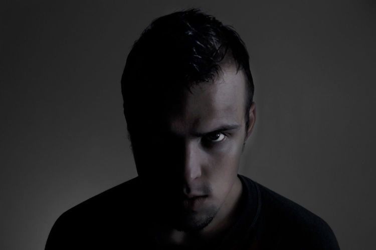 Portrait Of Angry Young Man Against Gray Background