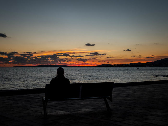 Silhouette Person Sitting On Bench By Sea Against Sky During Sunset