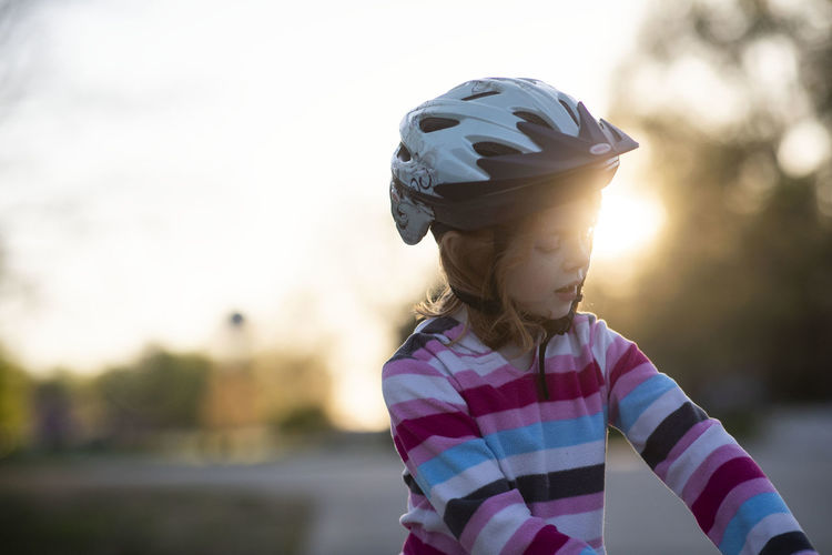 A five-year-old girl backlit by the sunset rides a bike during a late-spring evening while wearing a bicycle helmet. Childhood Child Focus On Foreground One Person Females Lifestyles Waist Up Casual Clothing Helmet Leisure Activity Girls Women Real People Headwear Nature Front View Standing Outdoors Innocence Bicycle Bicycle Helmet Sunset Glowing Backlight Bokeh Stripes Spring Springtime