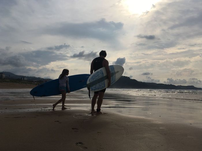 Father and daughter with surfboard walking at beach against sky