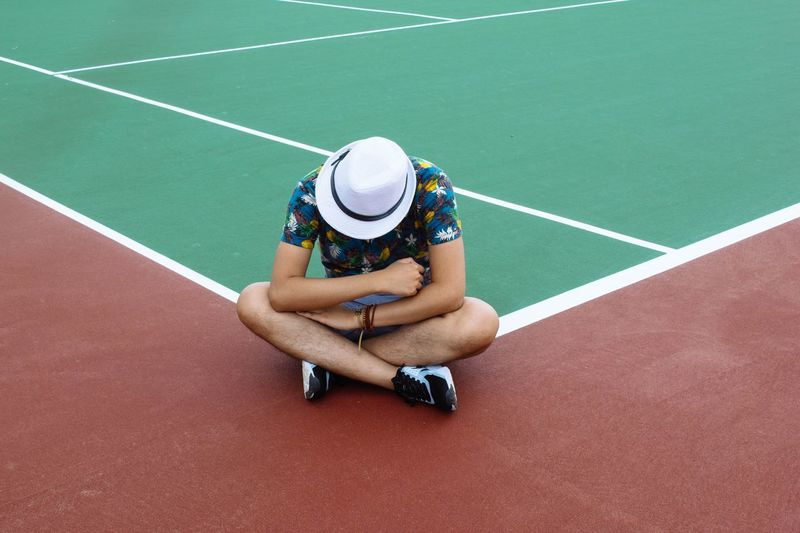 High angle view of man wearing hat while sitting on tennis court