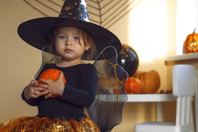 Full length of a girl holding hat