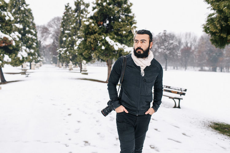 Handsome man with camera standing on snow covered footpath during winter