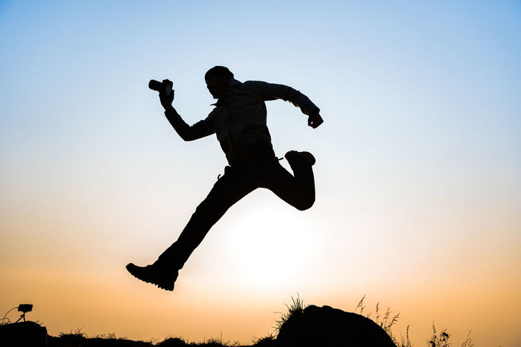 Arms Raised Child Clear Sky Enjoyment Full Length Human Arm Jumping Leisure Activity Lifestyles Men Mid-air Motion Nature One Person Real People Side View Silhouette Sky Sunset Vitality