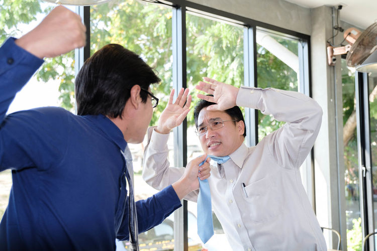 Angry Businessman Hitting Colleague At Cafe