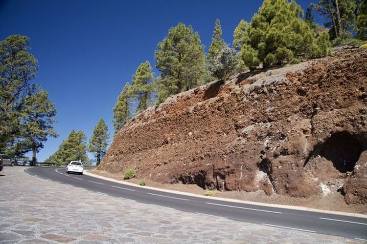 Road amidst rocks and trees against clear blue sky