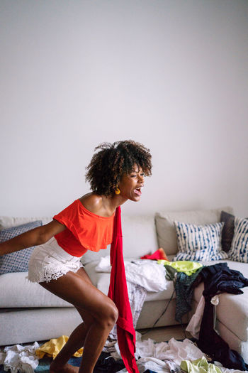 Black woman with afro hair throwing pile of clothing standing in the living room screaming