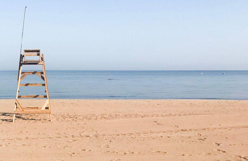 Lifeguard chair on sand at beach against clear sky