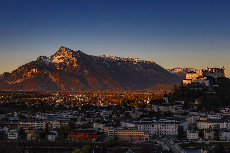 Aerial view of townscape by mountains against clear sky