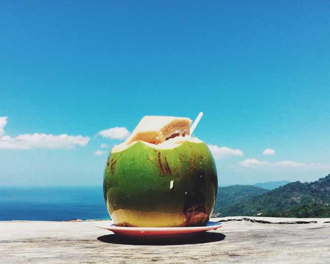 Coconut On Table By Sea And Mountains Against Sky