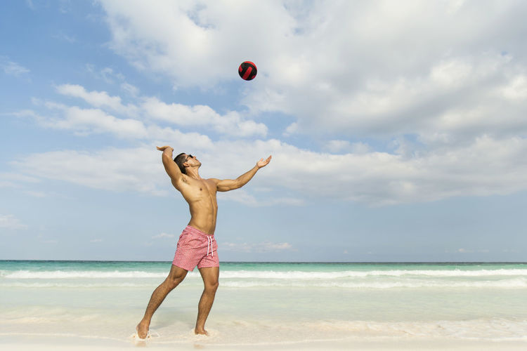 Shirtless man playing volleyball at beach against sky