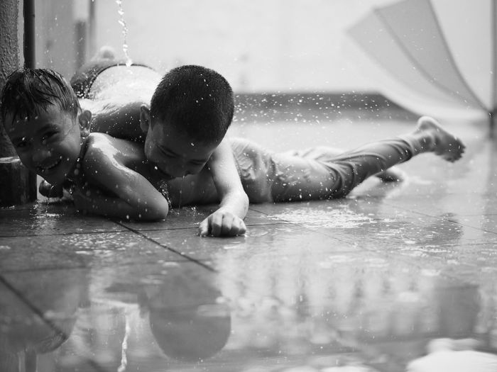 Shirtless Brothers Playing On Floor During Rain