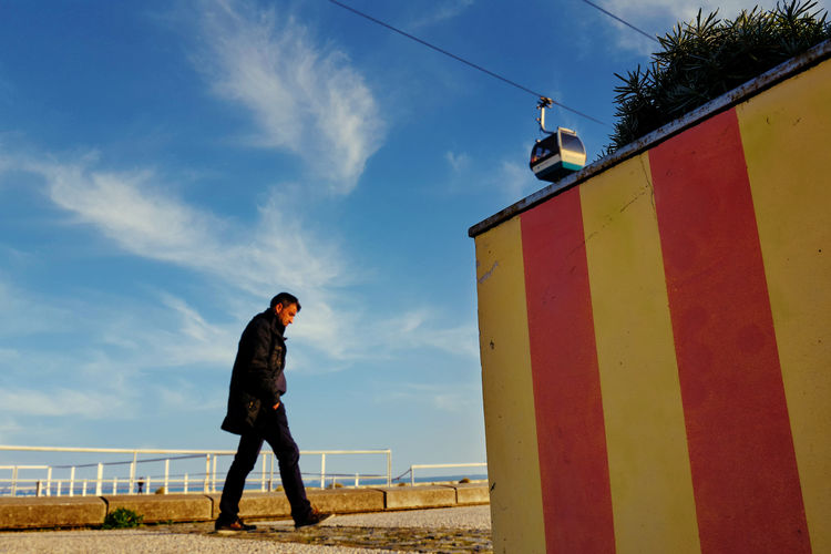 Low angle view of man standing on street against sky