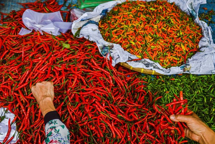 Cropped hand buying chili peppers
