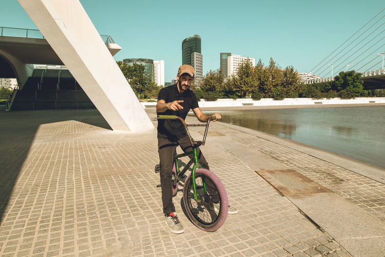 Man riding bicycle by water