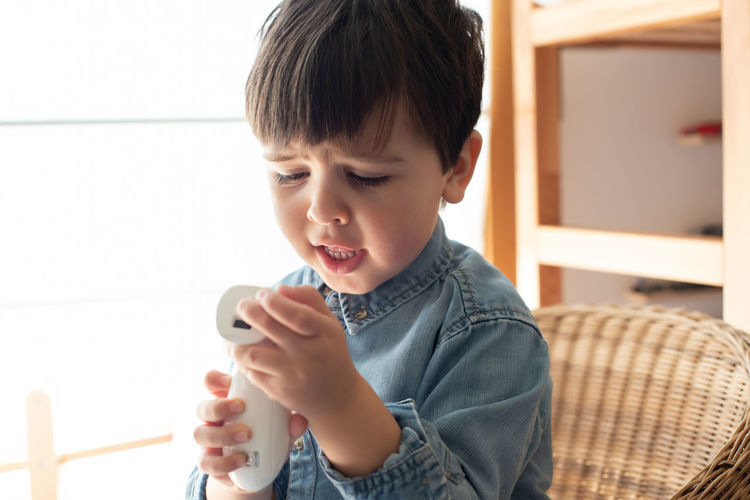 Boy holding mobile phone at home
