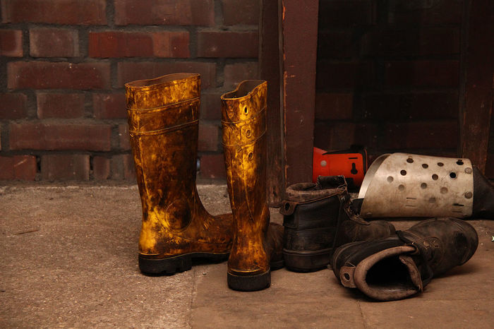 Boots covered in dirt left behind by workers No People Still Life Old Metal Built Structure Container Shoe Dirty Brick Focus On Foreground Close-up Wall Dirt Wall - Building Feature Side By Side Hard Work Coal Mine Work Boots Work Shoes  Call It A Day! End Of Working Day