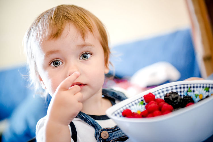 Close-Up Portrait Of Innocent Baby Girl Having Berries At Home