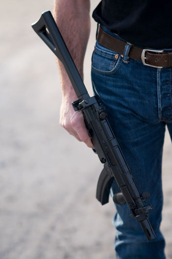 Cropped Image Of Man With Rifle Standing On Ground