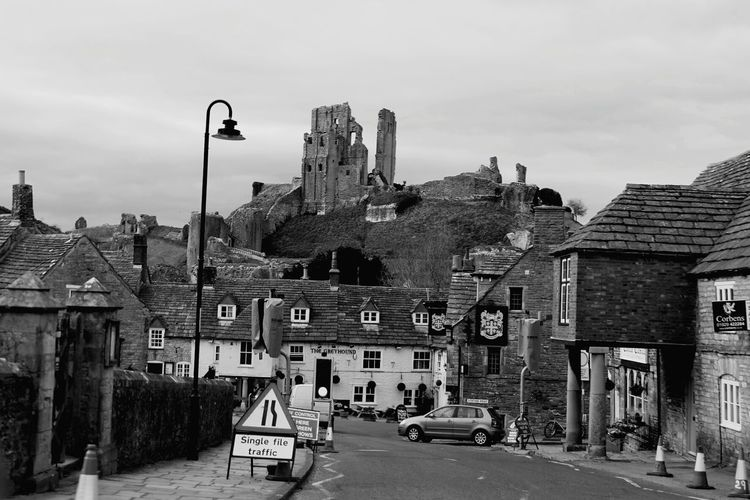 Road in town by corfe castle against sky