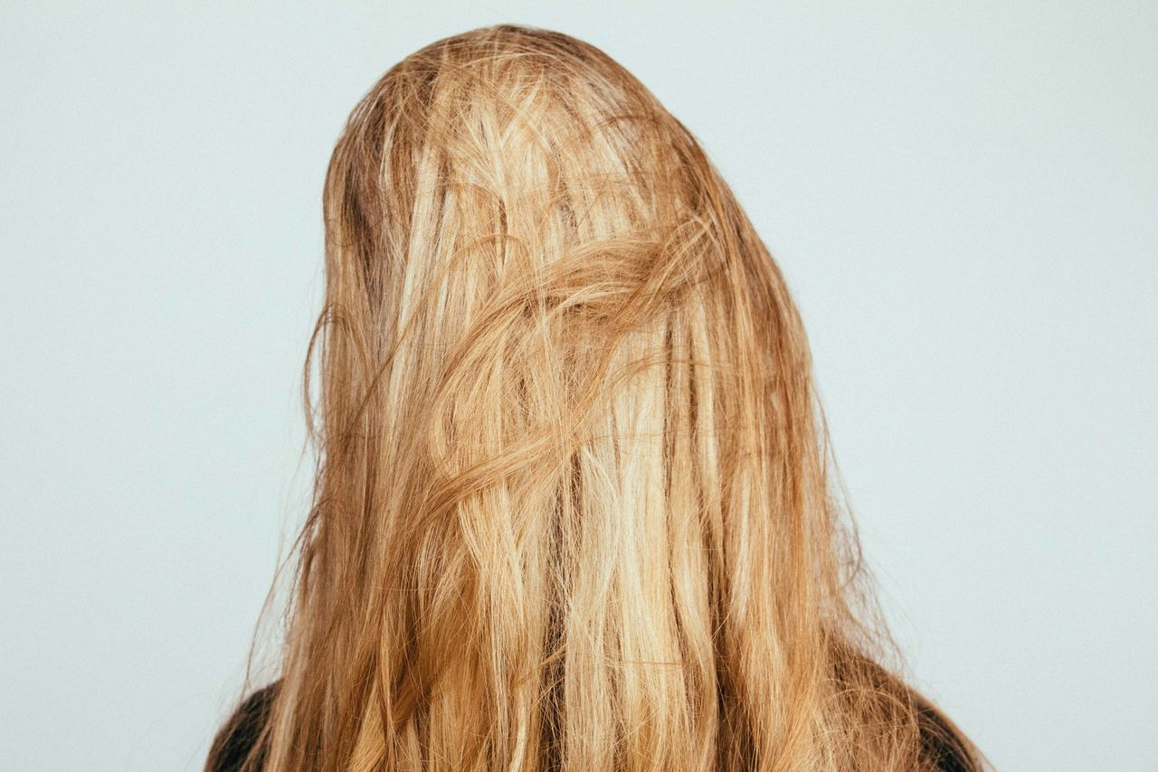 Rear view of blond woman against white background