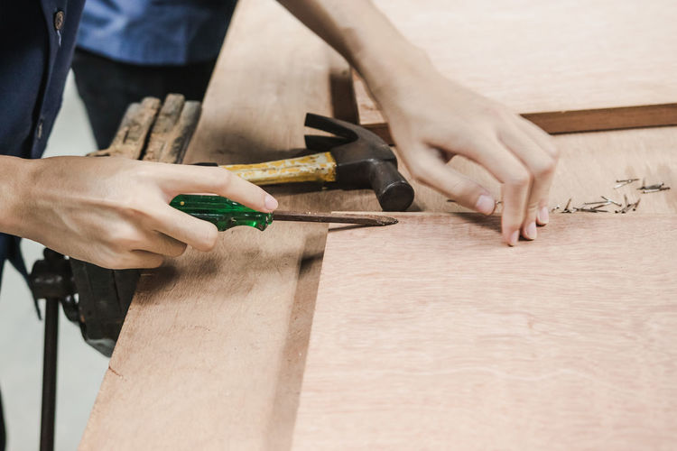 Cropped image of carpenter making furniture in carpentry workshop