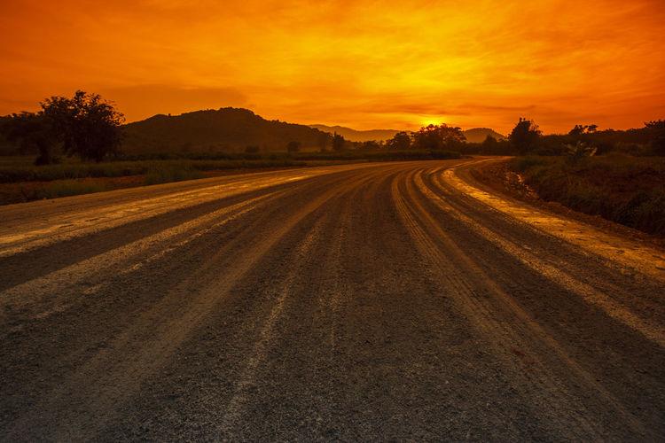 Dirt road amidst field against orange sky