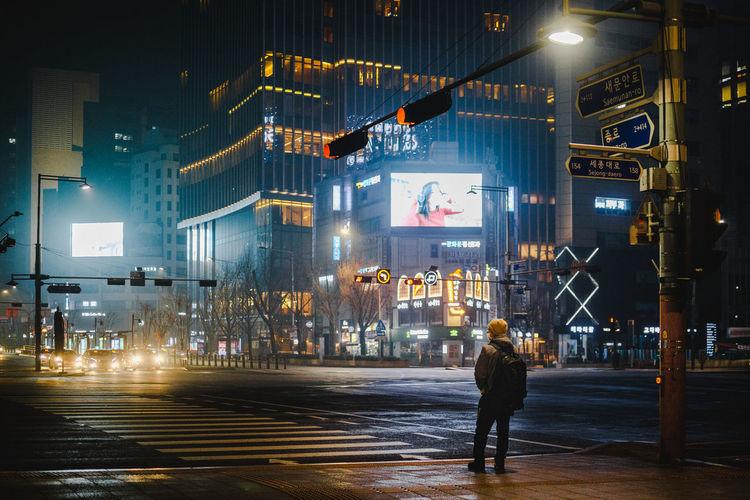 Rear view of people walking on illuminated city street at night