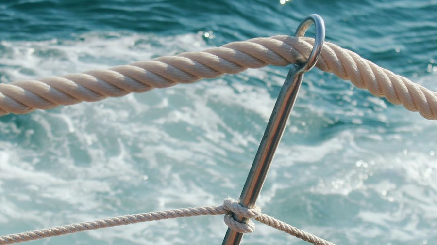 Close-up of rope tied to boat sailing in sea
