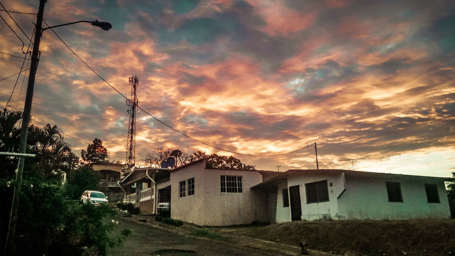 Houses against sky at sunset