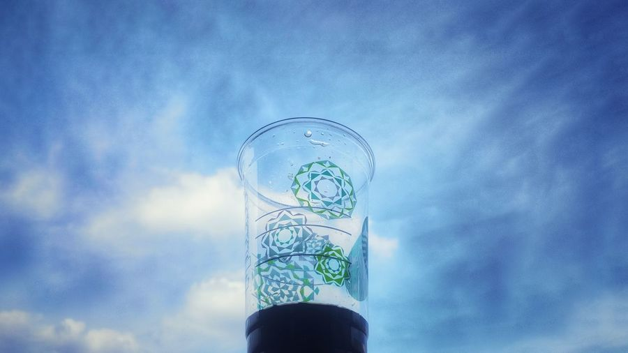 Low angle view of glass bottle against blue sky