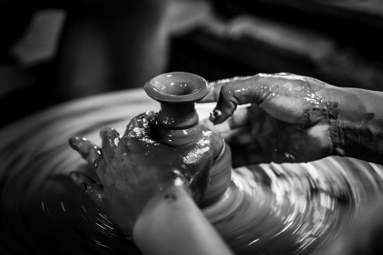 Cropped hands of person working on pottery wheel