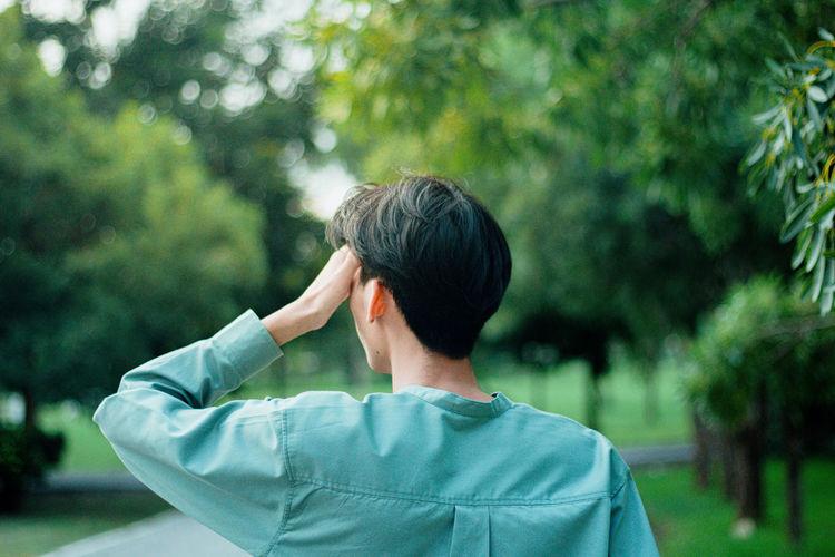 Rear view of senior man against trees