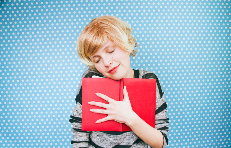 Young Woman Holding Book Against Blue Polka Dots Wall
