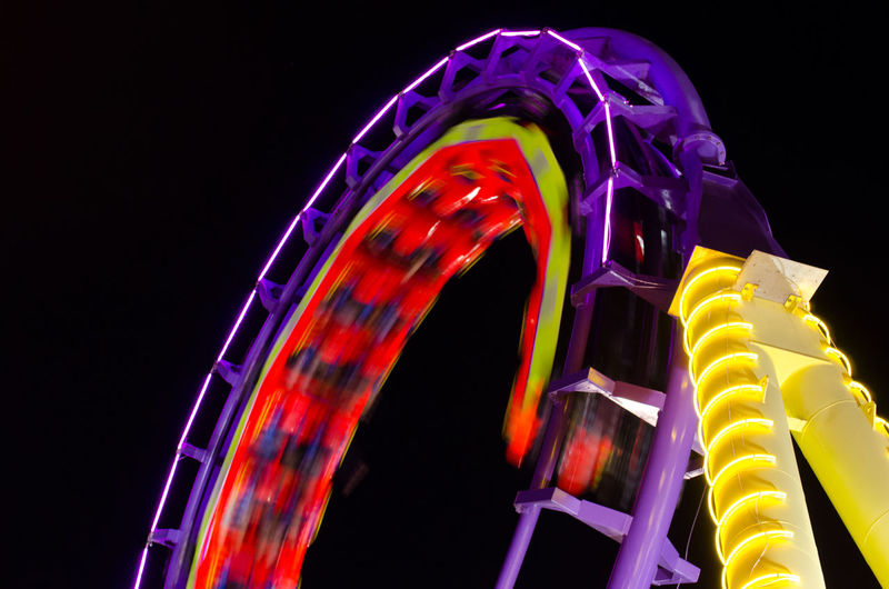 Blurred motion of illuminated rollercoaster at night