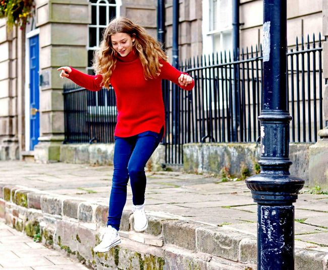 Young woman jumping from steps against fence