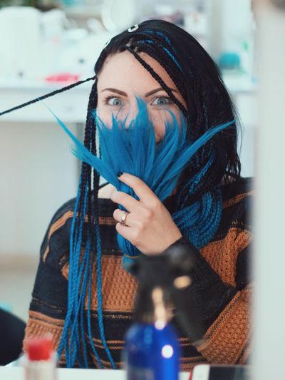 Portrait of woman holding dyed dreadlocks in salon
