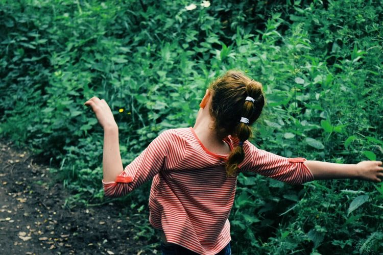 Rear view of girl with arms outstretched against plants