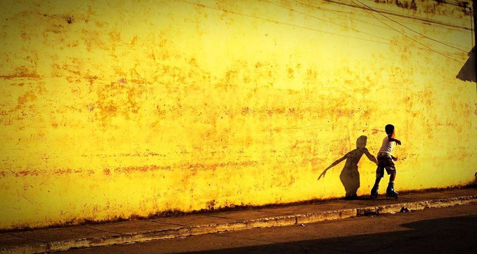 Shadow Streetphotography Trinidad, Cuba Travel Photography Travel Destinations Cuban Life Yellow Copy Space Wall - Building Feature Rollerskating Boys Office Building Exterior Real People Silhouette Water People Sunset Full Length Leisure Activity Sunlight Lifestyles Outdoors