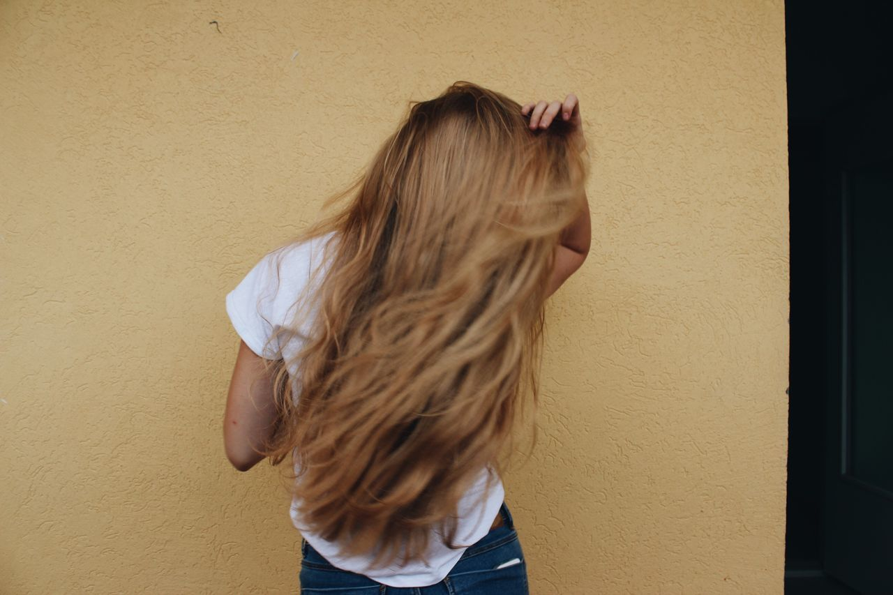Rear view of woman with tousled hair standing against wall