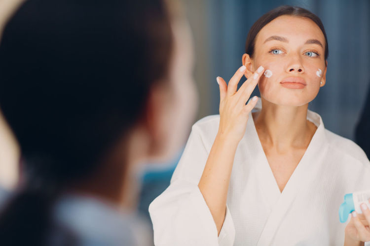 Young woman applying moisturizer on face