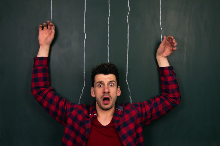Optical illusion of shocked man tied with ropes drawn on blackboard