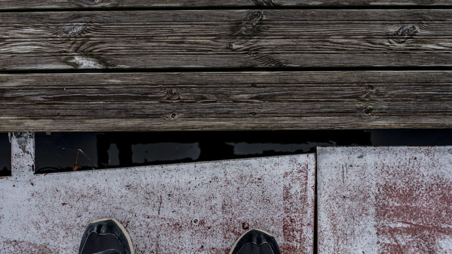 Low section of man standing on wooden plank