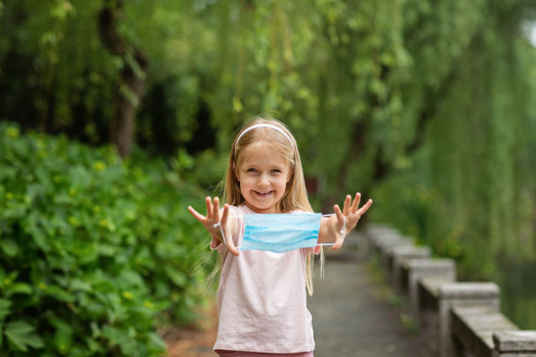 Portrait of smiling girl holding mask while standing outdoors