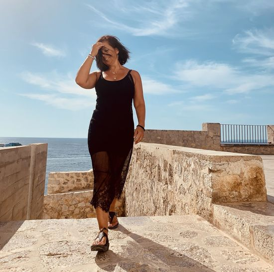 Full length of young woman standing against wall - ibiza